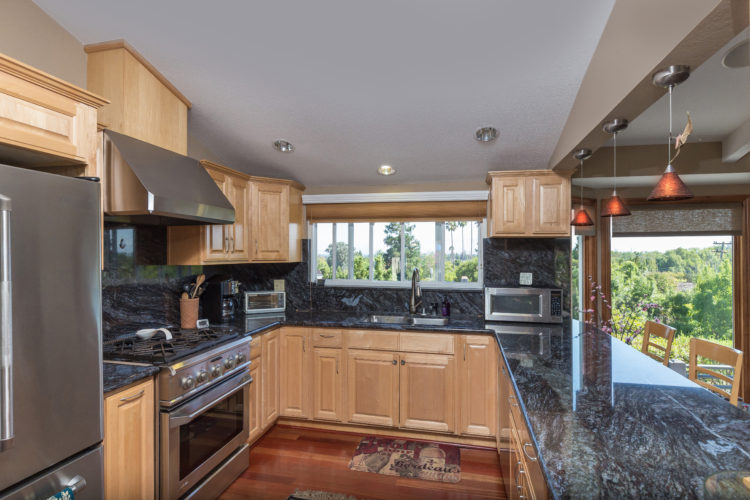 Slab granite counters and stainless steel appliances make for an appealing modern kitchen.